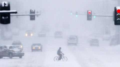 """Recent polling indicates most Americans believe human activities cause climate change but also shows the issue is less important to the public than the economy and other topics. A Gallup poll in March found that 34% of respondents think climate change, called global warming in the poll, posed a """"serious threat"""" to their way of life, compared with 64% who responded """"no."""" At the same time, more than 60% of respondents believed global warming was happening or would happen in their lifetime. Here, a pedestrian crosses Douglas Avenue on a bike during a snowstorm on February 4, in Wichita, Kansas."""