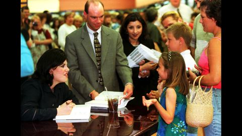 """Lewinsky speaks with young fans as she signs copies of her autobiography, """"Monica's Story,"""" in 1999."""