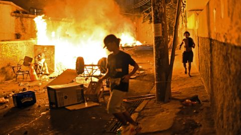 Residents run for cover during violent clashes between protesters and Brazilian Police Special Forces in a favela near Copacabana in Rio on April 22, 2014. Violent protests broke out in the city's landmark beachfront district following the death of a resident during clashes with the army in a nearby favela.