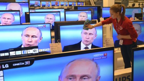 An employee wipes a TV screen in a shop in Moscow, on April 17, 2014, during the broadcast of President Vladimir Putin's televised question and answer session with the nation.