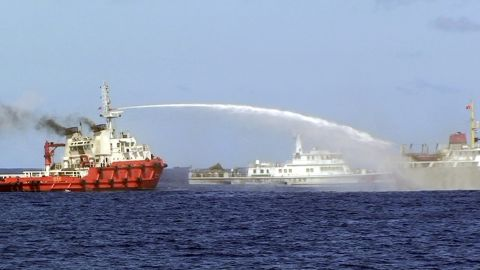In this photo released by Vietnam Coast Guard, a Chinese ship, left, shoots water cannon at a Vietnamese vessel, right, while a Chinese Coast Guard ship, center, sails alongside in the South China Sea, off Vietnam's coast, Wednesday, May 7, 2014. Chinese ships are ramming and spraying water cannons at Vietnamese vessels trying to stop Beijing from setting up an oil rig in the South China Sea, according to Vietnamese officials and video evidence Wednesday, a dangerous escalation of tensions in disputed waters considered a global flashpoint. (AP Photo/Vietnam Coast Guard)