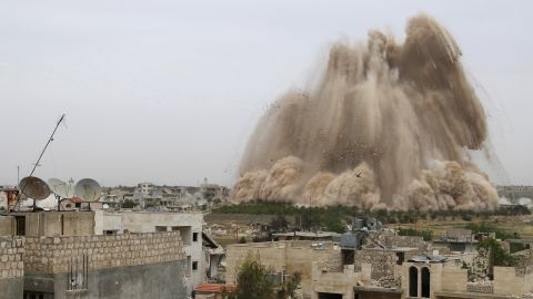 Debris rises in what Free Syrian Army fighters said was an operation to strike a checkpoint and remove government forces in Maarat al-Numan, Syria, on Monday, May 5.