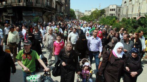 Residents carry their belongings in the al-Hamidieh neighborhood of Homs on May 10.