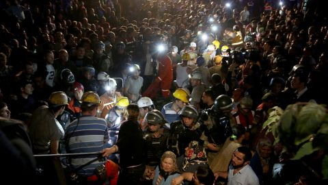 A massive crowd watches as rescuers work into the night.