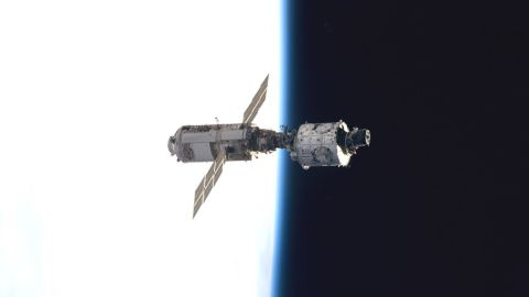 The Zarya control module, on the left with the solar panels, floats above Earth with its newly attached Unity module after the first assembly sequence in December 1998.