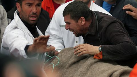 A man reacts as rescue workers carry the body of a miner from the mine in Soma, western Turkey, early Wednesday, May 14, 2014. Rescuers desperately raced against time to reach more than 200 miners trapped underground Wednesday after an explosion and fire at a coal mine in western Turkey killed at least 200 workers, authorities said, in one of the worst mining disasters in Turkish history. Turkey's Energy Minister Taner Yildiz said 787 people were inside the coal mine in Soma, some 250 kilometers (155 miles) south of Istanbul, at the time of the accident and 363 of them had been rescued so far. (AP Photo/Emrah Gurel)