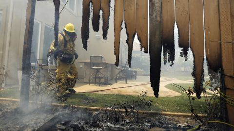 A firefighter puts water on a smoldering fence outside a home in Carlsbad on May 14.