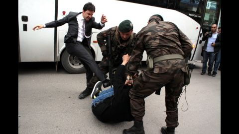 An aide to Turkish Prime Minister Recep Tayyip Erdogan kicks a person who is being wrestled to the ground by two police officers during protests in Manisa, Turkey, on Wednesday, May 14.
