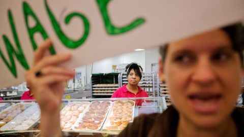 Krispy Kreme employee Beverly Ford looks on as demonstrators enter the store during a protest in Atlanta on Thursday, May 15. Calling for higher pay and the right to form a union without retaliation, fast-food chain workers around the globe participated in a strike.