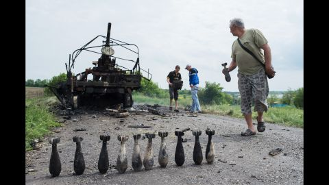 People collect mortar shells in front of a burnt-out Ukrainian military vehicle near Oktyabrskoe, Ukraine, on May 14.