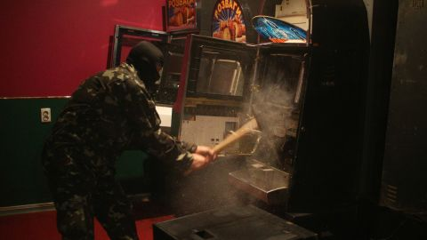 """A member of a """"self-defense"""" squad smashes a slot machine with a sledgehammer Monday, May 12, at an illegal club in Slovyansk."""