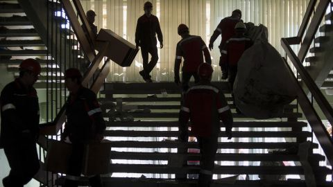 Employees of the Ukrainian company Metinvest clear away debris in a government building in Mariupol, Ukraine, on Friday, May 16, after pro-Russian separatists relinquished their hold on it.