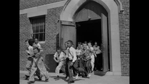 """Fourth-graders, both black and white, dash for the playground at St. Martin School in Washington on September 17, 1954. The Supreme Court ruling did not set a schedule for the integration of schools, rather calling for """"deliberate speed."""" The District of Columbia and four states acted to end segregation promptly, while other areas met with resistance."""