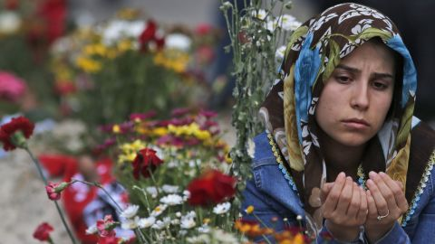 A relative offers her prayers next to the grave of a loved one in Soma on Friday, May 16.