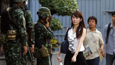 Office workers walk past armed soldiers outside the Shinawatra Tower Two office building in Bangkok on May 20.
