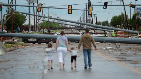 <strong>Then: </strong>Downed utility poles block the road on May 21, 2013.