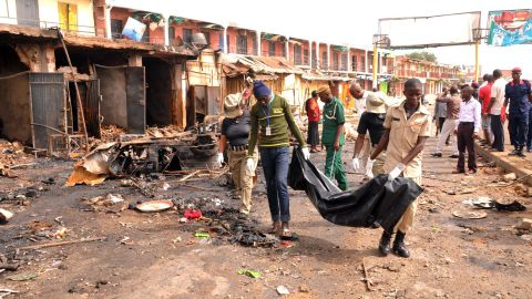 """Rescuers carry a body recovered from a burnt shop at the scene of twin bomb blasts at terminus market in the central city of Jos on May 21, 2014. Twin car bombings in central Nigeria killed at least 118 people and brought entire buildings down Tuesday, in the latest affront to the government's internationally-backed security crackdown. Nigerian President Goodluck Jonathan swiftly condemned the attack in the central city of Jos, calling it a """"tragic assault on human freedom"""" and condemning the perpetrators as """"cruel and evil"""". AFP PHOTO/ STRSTR/AFP/Getty Images"""