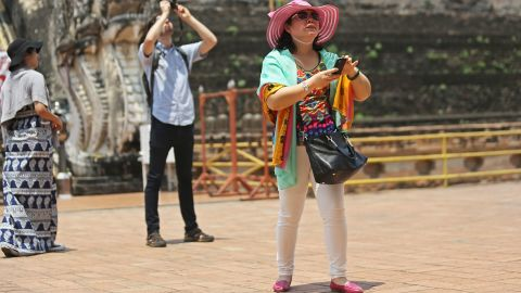 CHIANG MAI, THAILAND - APRIL 17: Chinese tourists take pictures at Wat Chedi Luang on April 17, 2014 in Chiang Mai, Thailand. Due to a rapidly growing economy, more than 100 million mainland Chinese are expected to go abroad this year. In Chiang Mai, which is seeing a surge in Chinese tourism after a popular Chinese movie was set there with a recent poll finding that 80% of residents were displeased with Chinese behavior while abroad. (Photo by Taylor Weidman/Getty Images)