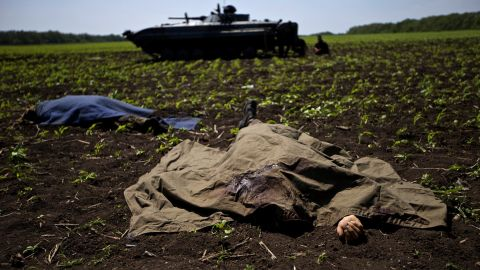 Bodies covered with blankets lie in a field near the village of Blahodatne, Ukraine, on May 22, as a Ukrainian soldier smokes next to his armored infantry vehicle.