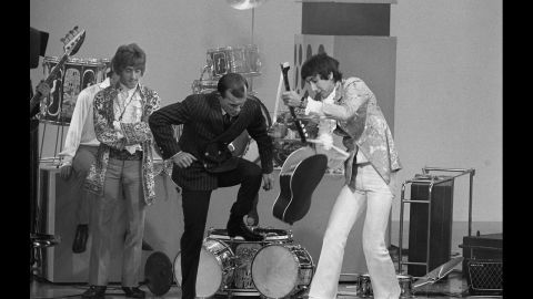 """""""The Smothers Brothers Comedy Hour"""" had a countercultural bent that regularly raised hackles -- and delighted fans. Here, The Who's Pete Townshend, right, helps host Tom Smothers destroy his acoustic guitar as singer Roger Daltrey looks on following The Who's performance of """"My Generation."""" The Smothers' battles with their network, CBS, would eventually lead to the show's cancellation."""