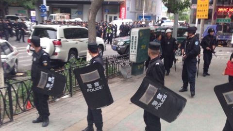 In this photo released by China's Xinhua News Agency, police officers stand guard near a blast site in  Urumqi, capital of northwest China's Xinjiang Uygur Autonomous Region.