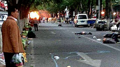 """Victims of a bombing lie on a street near the site where attackers ploughed two vehicles into a market and threw explosives, killing at least 31 people, in Urumqi in northwest China's Xinjiang region on May 22, 2014. More than 90 people were also wounded when two off-road vehicles drove into a crowd in Urumqi, with one of them exploding, the regional government's Tianshan web portal said, in what authorities called the latest """"severe terrorist incident"""" to hit the Muslim Uighur homeland. CHINA OUT AFP PHOTO/STRSTR/AFP/Getty Images"""