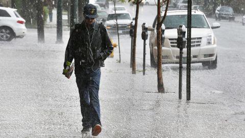Robert Teran walks to work as hail falls over downtown Denver on May 22.