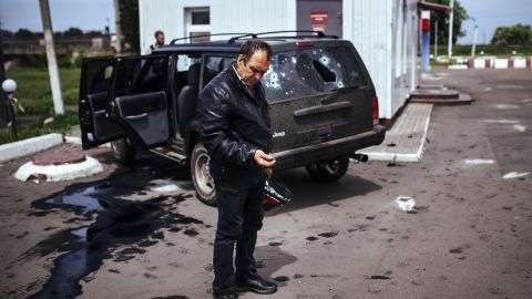 A man looks at a bullet shell next to a destroyed car after a gunfight between pro-Russian militiamen and Ukrainian forces in Karlivka, Ukraine, on Friday, May 23.