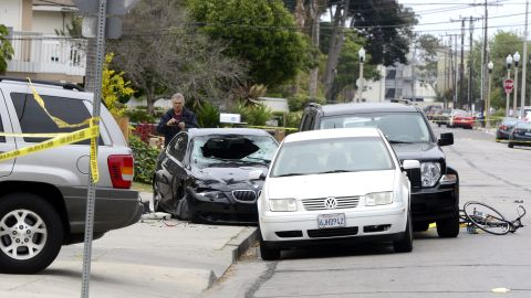 """A police officer inspects the gunman's car on May 24 after the killing spree in Isla Vista. The suspect, described as mentally disturbed and possibly bent on retribution, sprayed bullets from his car in a rampage called """"premeditated mass murder,"""" Santa Barbara County sheriff's deputies said."""