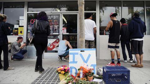 Flowers are left on the sidewalk of the IV Deli Mart in Isla Vista, California.