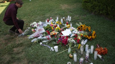 A man places flowers on the lawn of the Alpha Phi sorority house May 25, 2014 in Isla Vista, California.