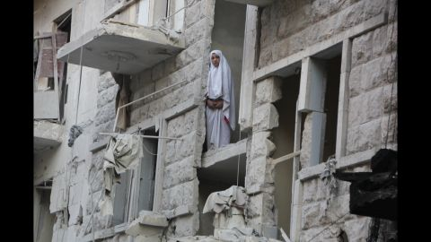 A woman stands in a heavily damaged building in Aleppo on May 26.
