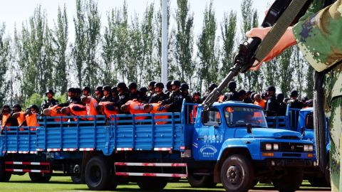 Terror suspects, in orange jumpsuits, held by security forces.