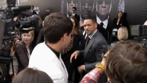"""Will Smith walks away after slapping Sediuk, white jacket, who had just tried to kiss him, on the red carpet of the premiere of """"Men in Black III"""" in Moscow in 2012."""