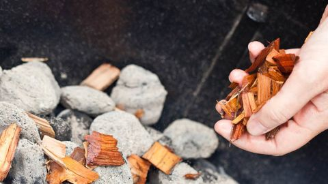 Sprinkle soaked wood chips over coals.