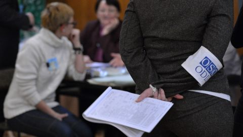 An election observer of the Organization for Security and Cooperation in Europe (OSCE) stands as electoral commission members count ballots at polling station in Kiev on October 28, 2012.