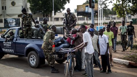 Members of the Central African Republic's National Gendarmerie help to carry a wounded civilian off his bike onto a truck heading to the hospital in the central district of Bangui on May 29, 2014. At least 15 people, including a priest, were killed and several others wounded in clashes on the eve in the capital of the strife-torn Central African Republic, a military source said.