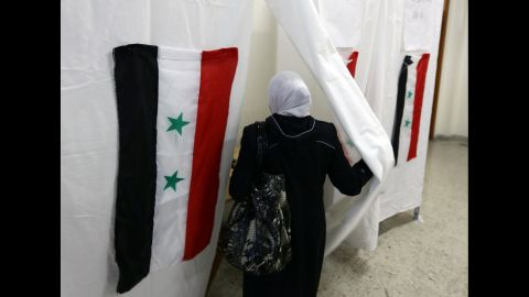 """The Syrian flag is seen hanging on a polling booth as a Syrian woman heads to cast her ballot in the presidential election on June 3, 2014 at a polling station in Damascus. Voting offices opened in Syrian regime-held areas for a presidential election that current President Bashar al-Assad is certain to win, and that has been slammed as a """"farce"""" by the opposition. AFP PHOTO/ LOUAI BESHARA        (Photo credit should read )"""