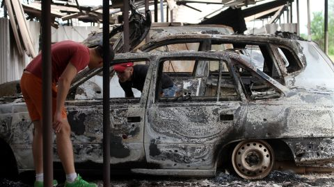 Teenagers examine burned cars near a Federal Border Headquarters building in the eastern Ukrainian city of Lugansk on June 3, 2014.