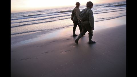 World War II re-enactors walk along Omaha Beach in Vierville sur Mer, France, on Friday, June 6, the 70th anniversary of D-Day.