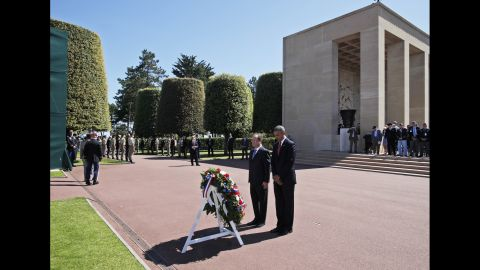 President Barack Obama and French President Francois Hollande pause for a moment of silence after laying a wreath at the Normandy American Cemetery in Colleville sur Mer, France, on Friday, June 6, the 70th anniversary of D-Day.