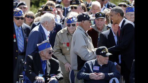President Obama greets veterans during the D-Day ceremony in Colleville-sur-Mer.