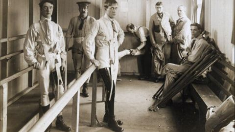 Postcard of British soldiers using parallel bars to help them learn to walk with their artificial legs. Image was probably taken at Queen Mary's Convalescent Auxiliary Hospital, a specialized orthopedic hospital that opened in London in 1915.