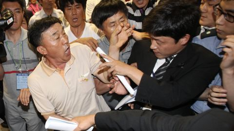 """Family members of passengers onboard the sunken ferry Sewol struggle with a security officer (R) while attempting to attend the murder trial of the captain and crew from the sunken ferry Sewol at the Gwangju District Court in the southwestern South Korean city of Gwangju on June 10, 2014. Captain Lee Joon-Seok and three crew members are accused of """"homicide through wilful negligence"""" -- a charge that falls between first-degree murder and manslaughter, but still carries the death penalty. Eleven other members of the crew are being tried on lesser charges of criminal negligence and violations of maritime law. The Sewol was carrying 476 passengers, including 325 students on a school trip, when it sank off the southwest coast on April 16. AFP PHOTO / POOL / Ahn Young-joonAHN YOUNG-JOON/AFP/Getty Images"""