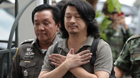 Thai anti-coup activist Sombat Boonngamanong (C) gestures as he arrives escorted by police and soldiers at a military court in Bangkok on June 12, 2014. The prominent anti-coup activist faces up to 14 years in prison if convicted of incitement, computer crimes and ignoring a summons by the junta, police said on June 12.    AFP PHOTO / Christophe ARCHAMBAULT        (Photo credit should read CHRISTOPHE ARCHAMBAULT/AFP/Getty Images)