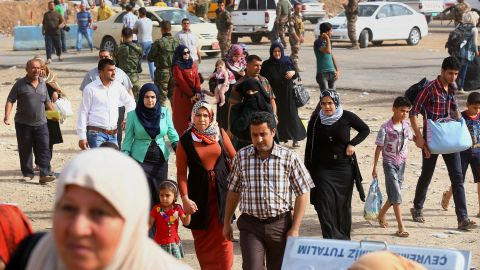 Iraqi refugees pass an area in Erbil on June 12.