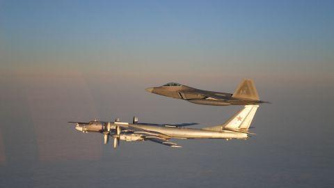 A U.S. Air Force F-22 Raptor, top, escorts a Russian Air Force Tu-95 bomber off the coast of Alaska in 2011.