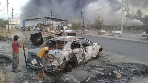 Children stand next to a burnt vehicle during clashes between Iraqi security forces and ISIS militants in Mosul on Tuesday, June 10.