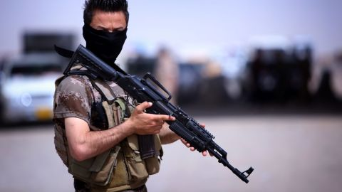 A masked Pershmerga fighter from Iraq's autonomous Kurdish region guards a temporary camp set up to shelter Iraqis fleeing violence in the northern Nineveh province, in Aski kalak, 40 kms west of the region's capital Arbil, on June 13, 2014. Thousands of people who fled Iraq's second city of Mosul after it was overrun by jihadists have been queuing in the blistering heat, hoping to enter the safety of the nearby Kurdish region and furious at Baghdad's failure to help them. AFP PHOTO/SAFIN HAMED        (Photo credit should read SAFIN HAMED/AFP/Getty Images)
