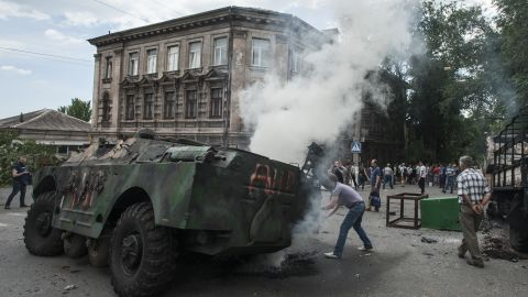 Locals in Mariupol gather around a burning military vehicle at the site of a battle between Ukrainian troops and pro-Russian fighters on June 13.